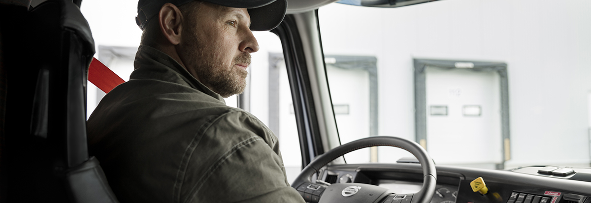 Person with a cap driving a Volvo Truck - VO-DRIV-16-0001