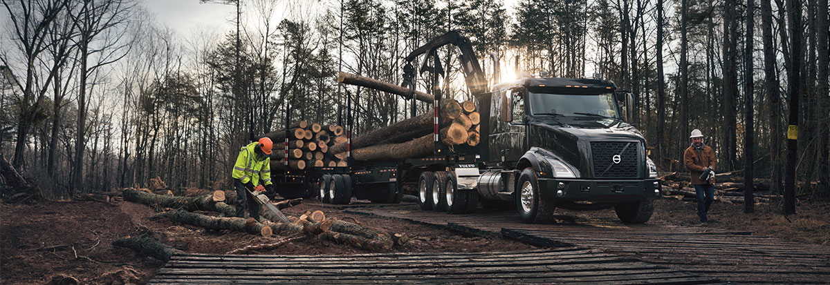 Men are loading logs of wood on a Volvo Truck VNX - heavy haul