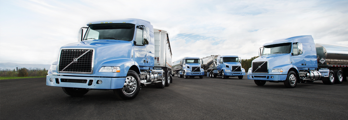 four Volvo Trucks VNR on an empty road