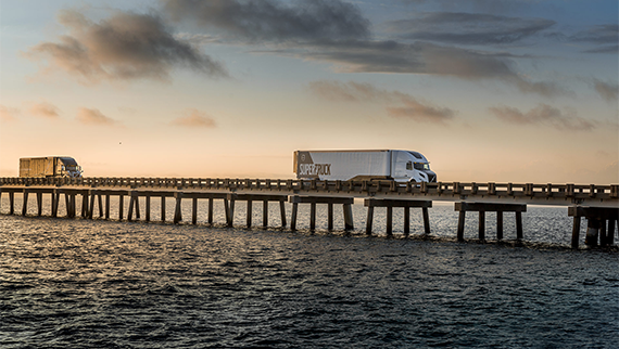 Volvo SuperTruck driving on a bridge over a river