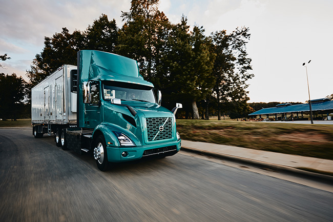Volvo-VNR-Electric-6x2-Tractor-with-Reefer-Trailer-Passenger-Side-View-on-the-Road-Daytime-Shot-2