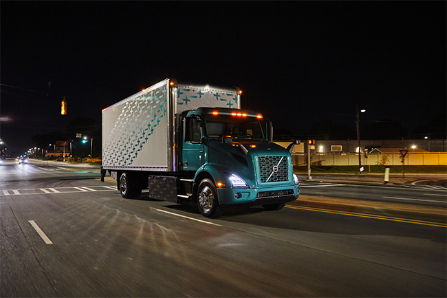 Volvo VNR Electric On the Road Nighttime Image Passenger Side with Batteries Bright